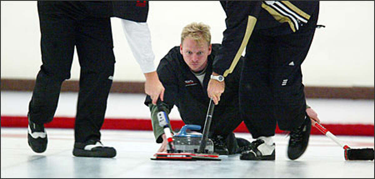 Team Larway's Bart Sawyer throws the rock during a tournament at the Seattle Granite Curling Club. Teammates sweep to guide the rock.