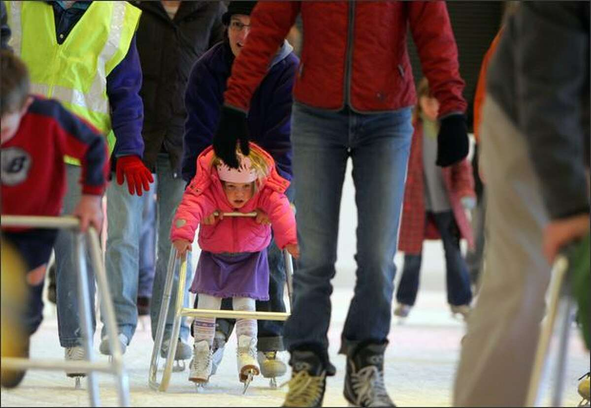Three-year-old Alexandra Fiske, visiting Seattle from Oakland, Calif., skates with the aid of a walker at Seattle Center during the first day of Winterfest 2007, a seasonal event that runs through Jan. 6, in Seattle.