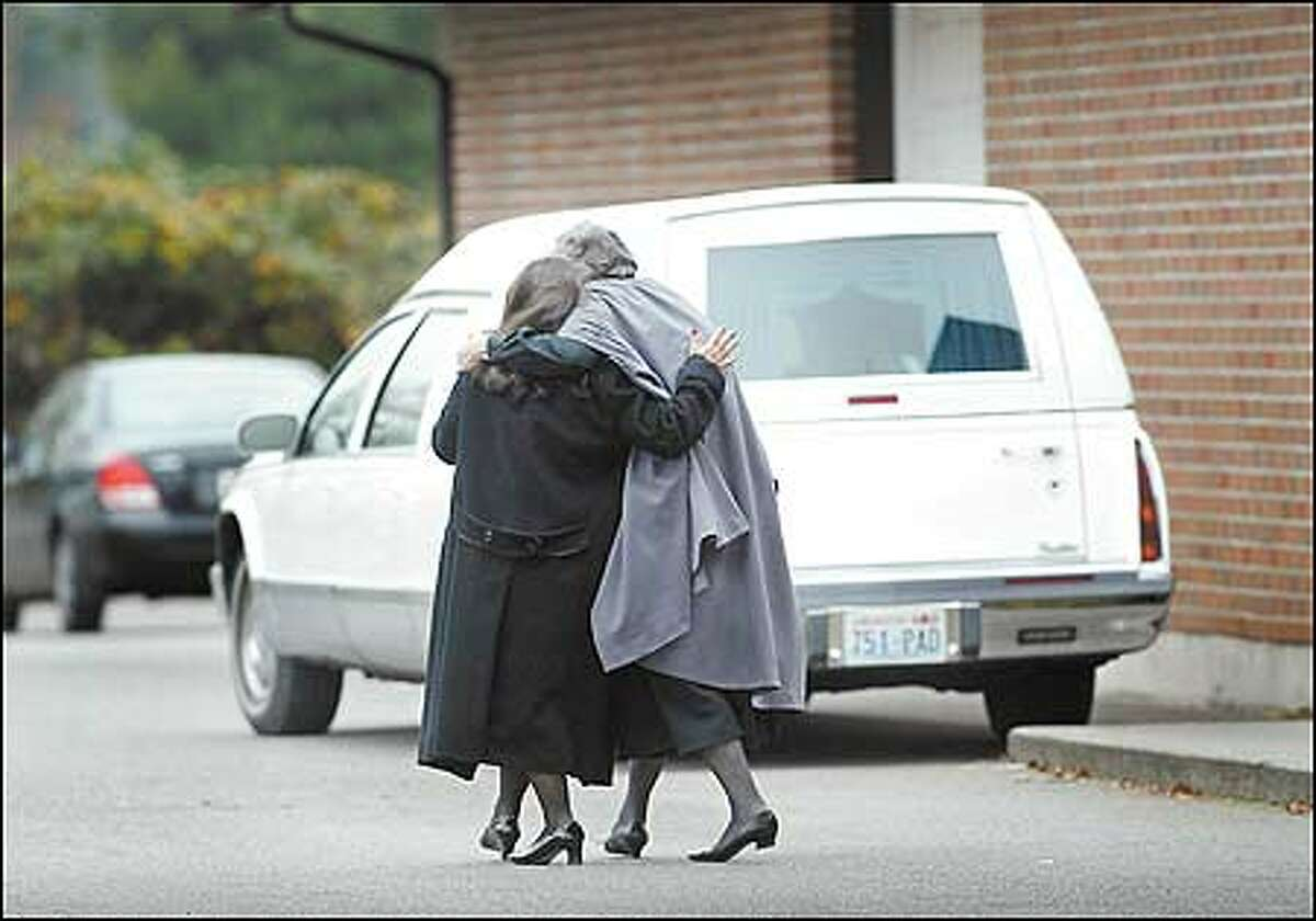 Mourners pass a hearse after leaving the funeral for Justice and Raiden Robinson at First Church of the Nazarene in Bremerton yesterday.
