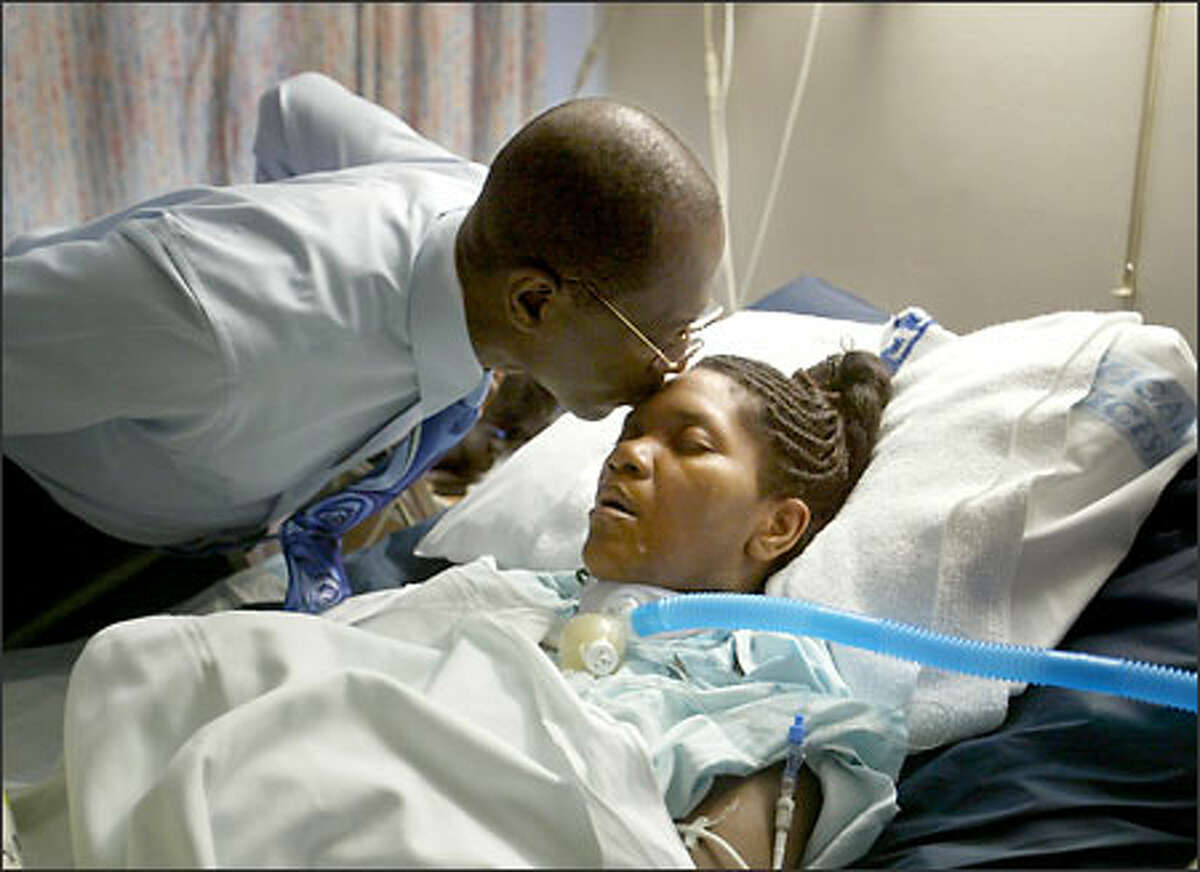 Calvin Jones kisses his daughter, Kim Jones, who has been in a coma since Nov. 12, 2002, when she had what was supposed to be routine surgery.
