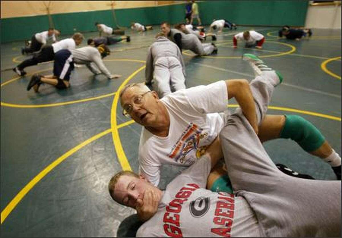 Bishop Blanchet wrestling coach Bill Herber demonstrates a move on junior Sam McNaghten.