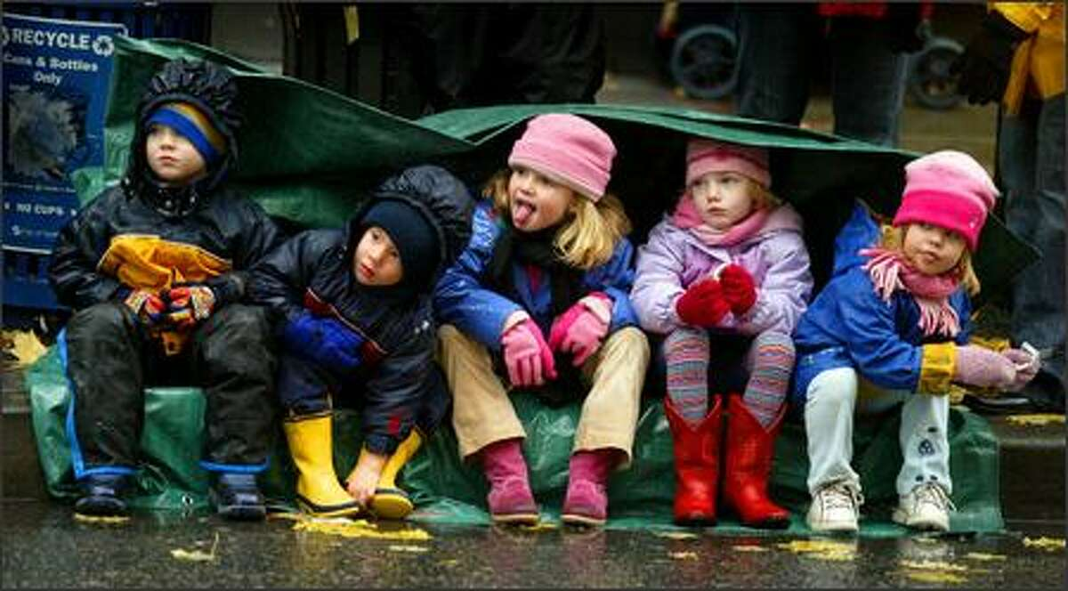 Constant rainfall didn't stop Ryan Klee, 6, and Owen Klee, 3, of Bothell, Hailey Holm, 6, of Buckley, Declan Chapin, 4, of Mercer Island, and Kaitie Holm, 4, of Buckley, from taking in the sights and sounds along Fifth Avenue at the annual Macy's Holiday Parade in downtown Seattle Friday.