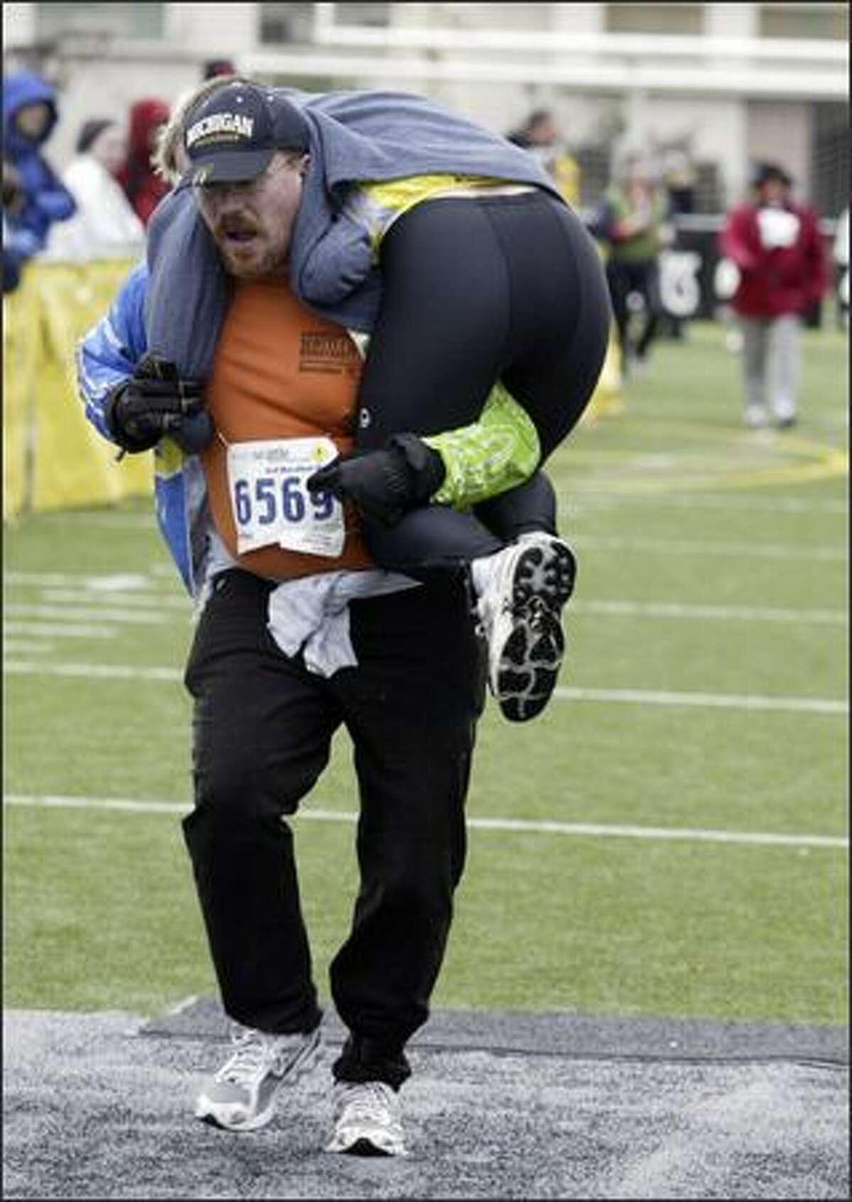 Wendell Joost carries his wife Hobbin across the finish line of the 26.1-mile walk event during the 2006 Seattle Marathon.