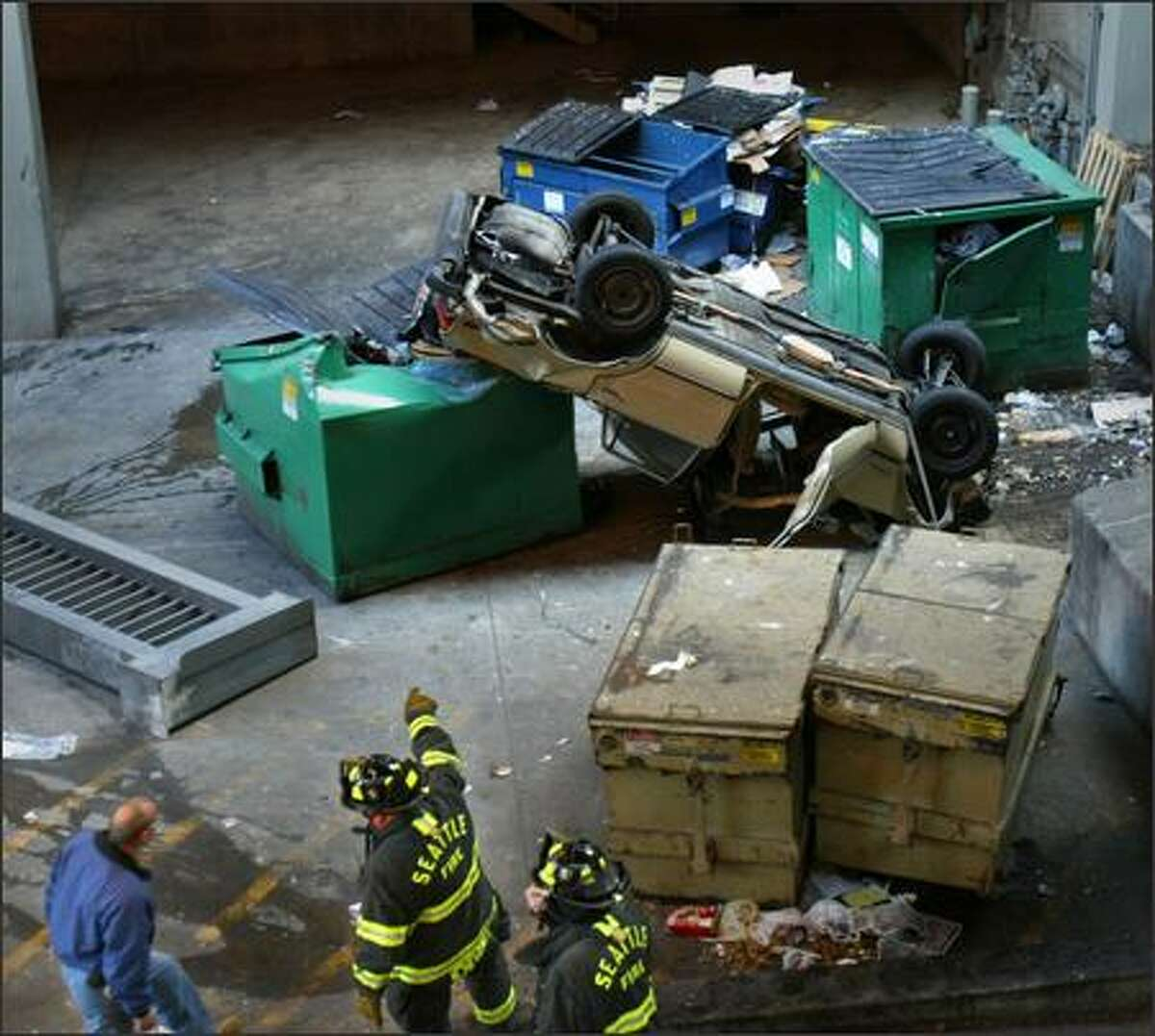 Firefighters point to an overturned car that plunged off a downtown road and onto a berm and a garbage bin Monday.