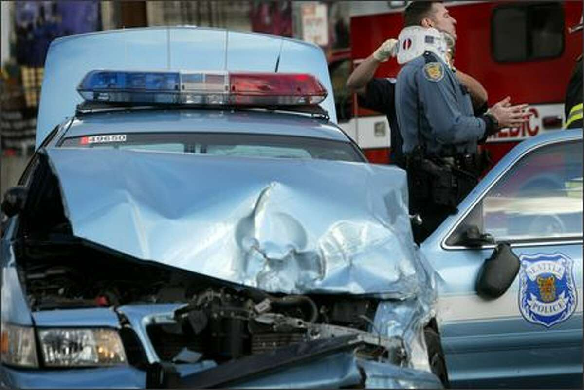 A paramedic treats a police officer injured in a collision with a pickup truck about 2:45 p.m. Monday at Denny Way and Queen Anne Avenue North as the officer was en route to help a fellow officer on a traffic stop. The pickup driver also was injured in the crash.