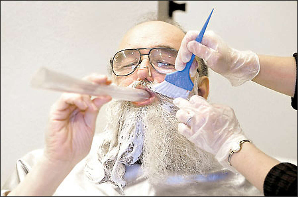 Neil Beck, 58, of Kirkland, puts a lot of work into his transformation into Santa. Here he breathes through a plastic tube to avoid the harsh fumes while having his beard bleached white at McLaughlin Hair Design in Seattle. It takes two treatments to get the desired look before Beck is ready to resume his role at Bellevue Square Mall.
