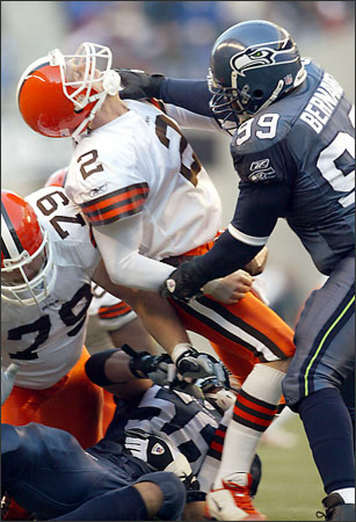 Seahawks DE Rocky Bernard, hitting Tim Couch high, and Chike Okeafor, hitting him low, knock the Browns quarterback out of the game.
