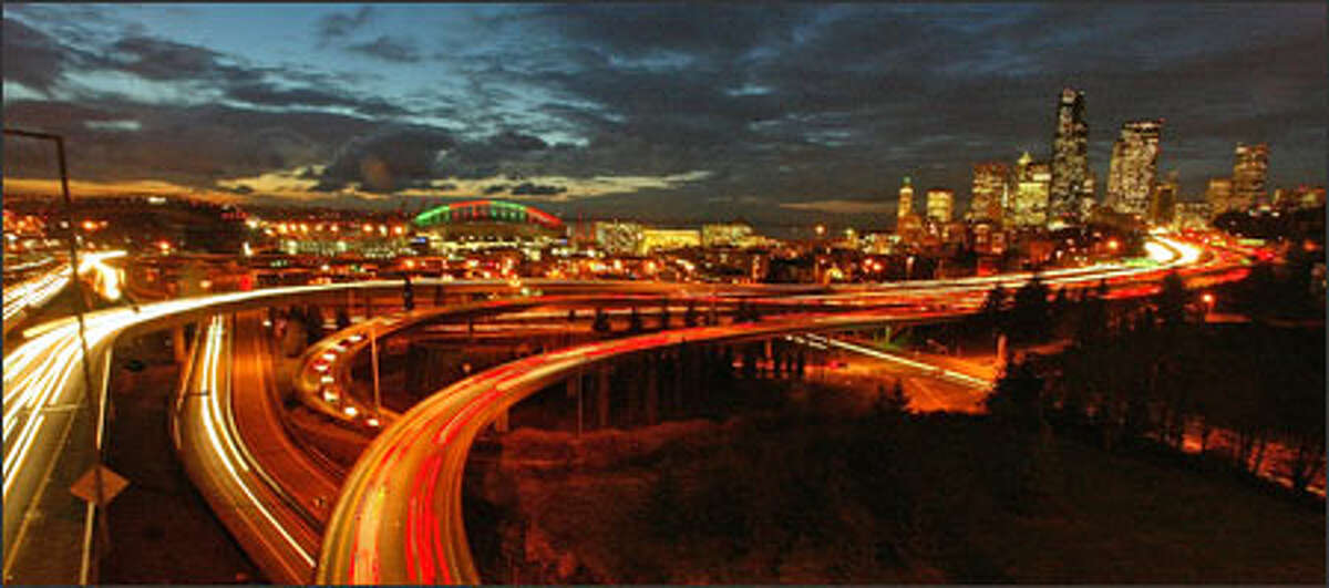 A slow shutter speed captures early-evening traffic moving through Seattle Wednesday, as seen from the 12th Avenue South Bridge.