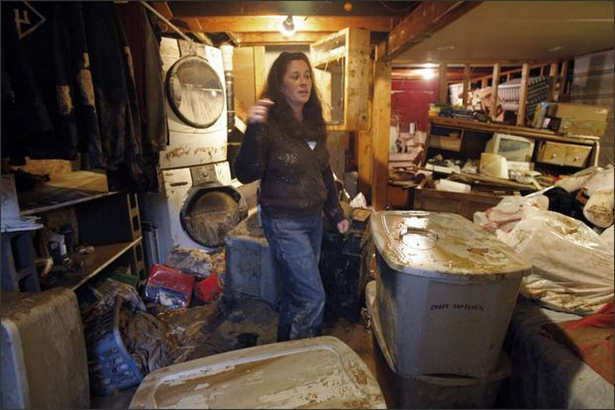 Kem Stokes surveys the damaged to her master bedroom after it was damaged by water when a 16-inch water main ruptured near her home at 10418 26th Ave. S.W. Seattle.