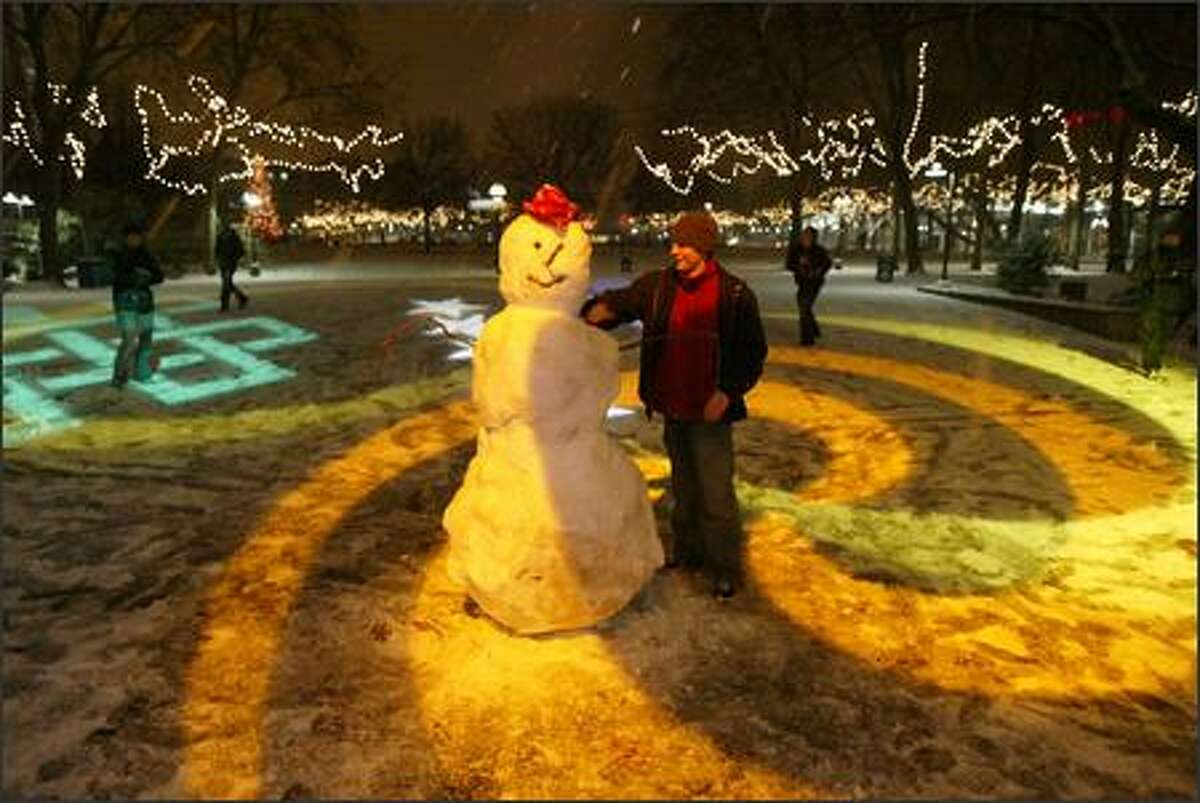 Passersby enjoy the company of a friendly snowman outside KeyArena Wednesday night.