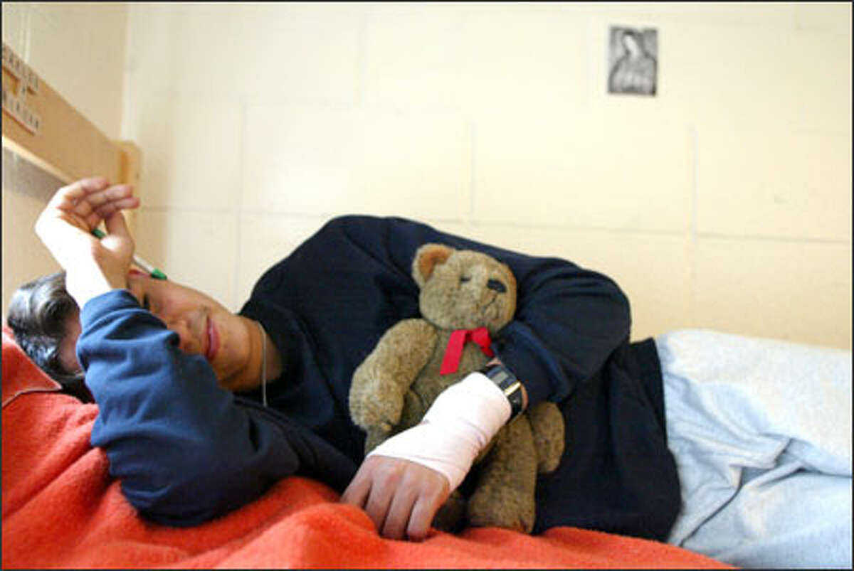 """Salvadoran teen """"Tayo"""" cradles a teddy bear given him by a staff member at a locked residential facility in Fife for undocumented children picked up by immigration authorities."""