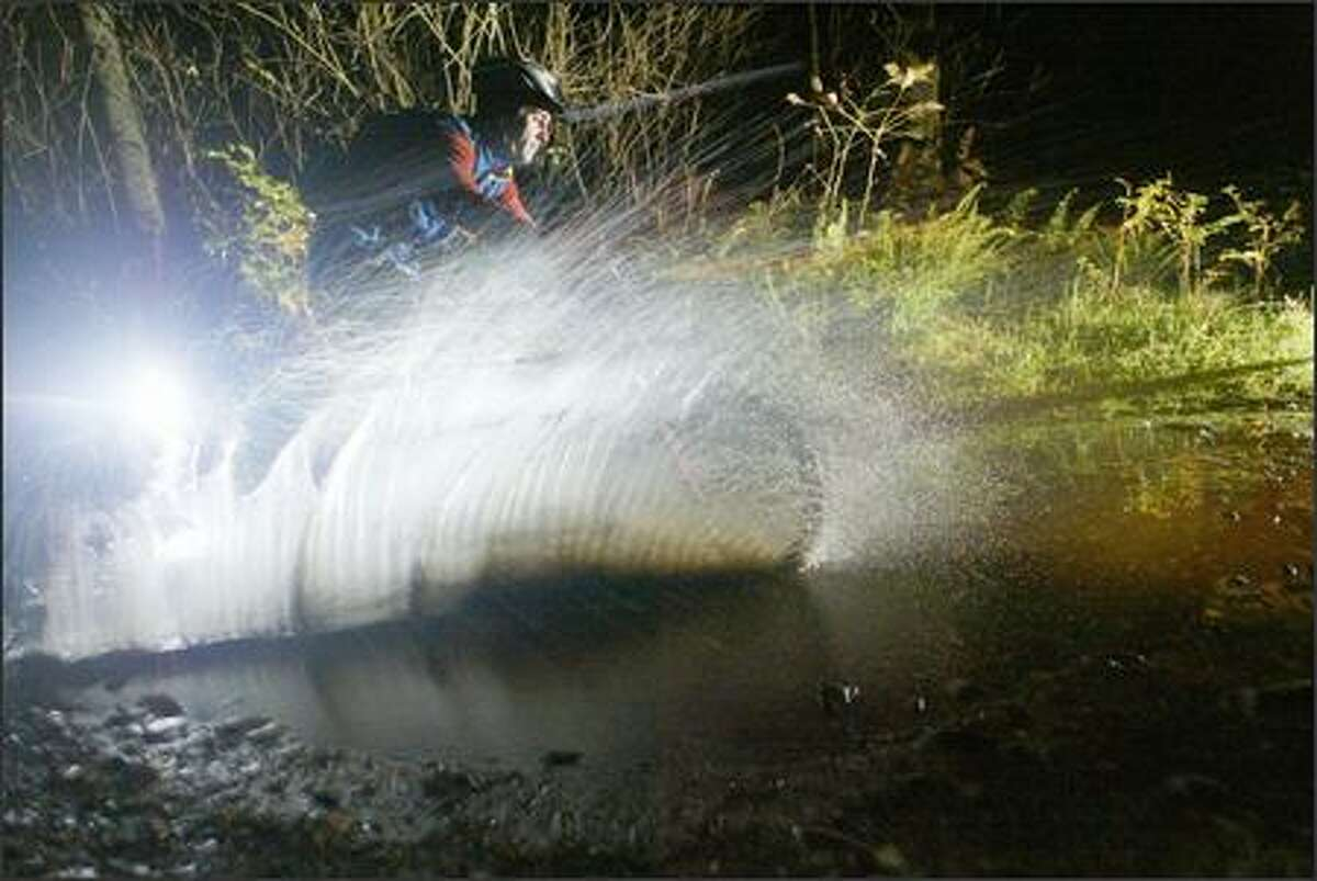 Doug Nathe plows through a mud puddle during a night mountain-bike ride near Fall City.