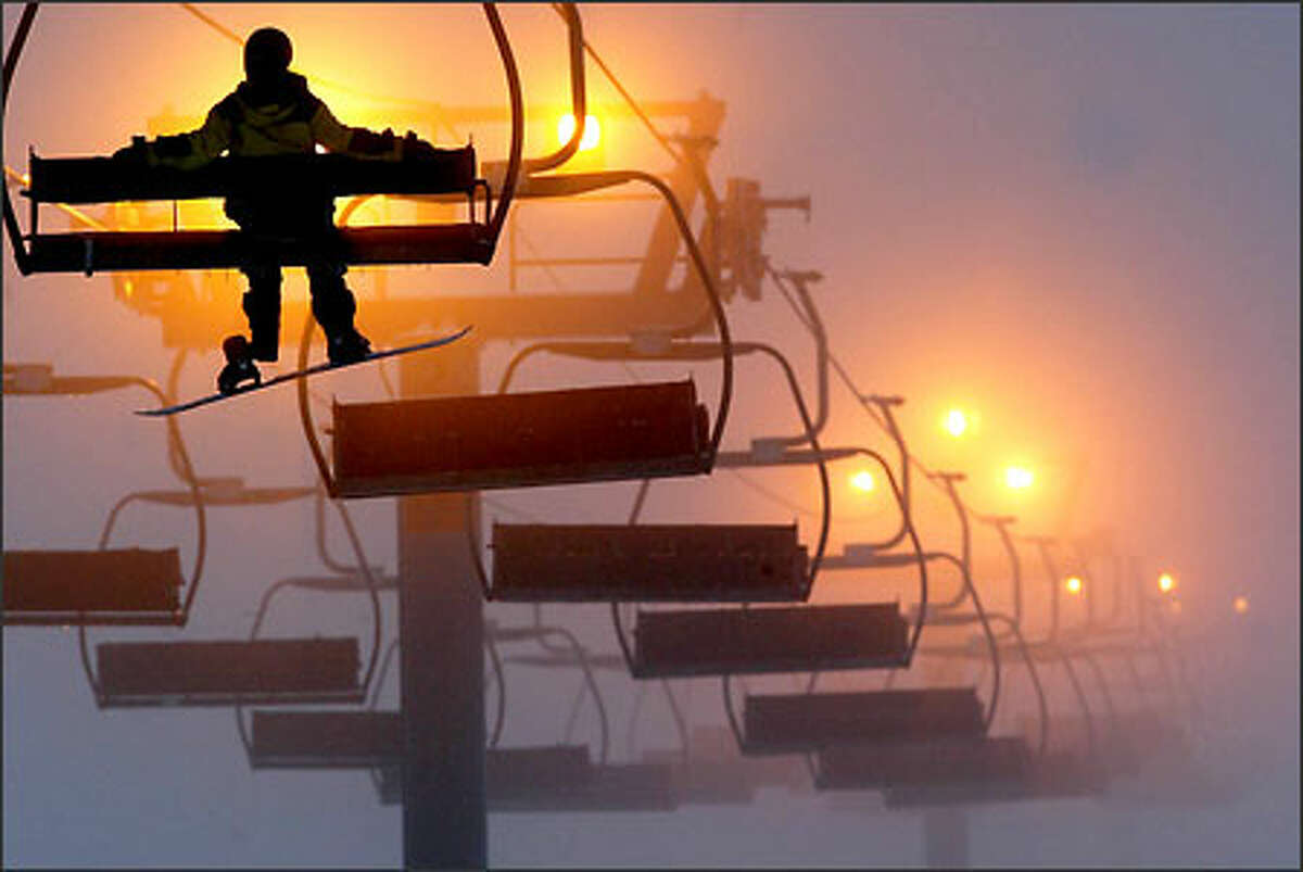 A snowboarder rides a lift at dusk on part of The Summit at Snoqualmie Pass. The region's lowest ski resort, it is most at risk from global warming's effect on the snow line.