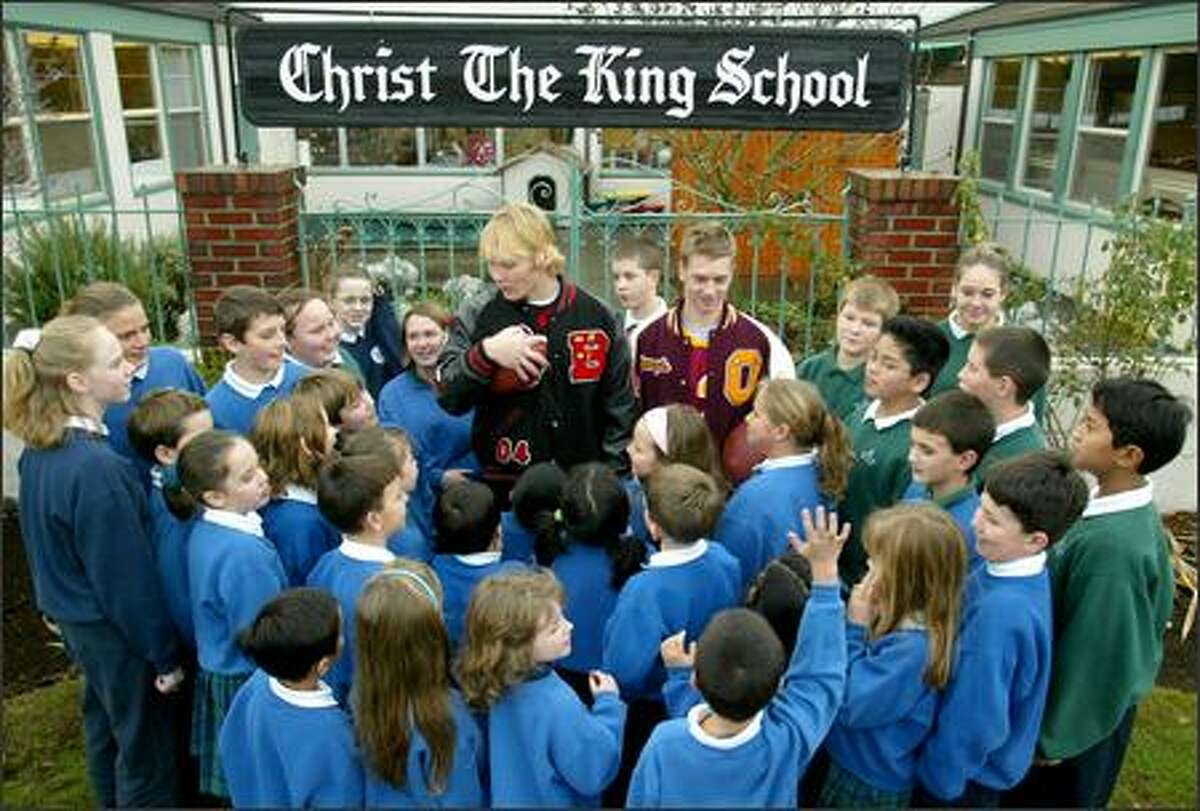 Quarterbacks Cole Morgan from Ballard, left, and Joey Shanks of O'Dea meet with students at Christ the King School, where the football players were once schoolmates.