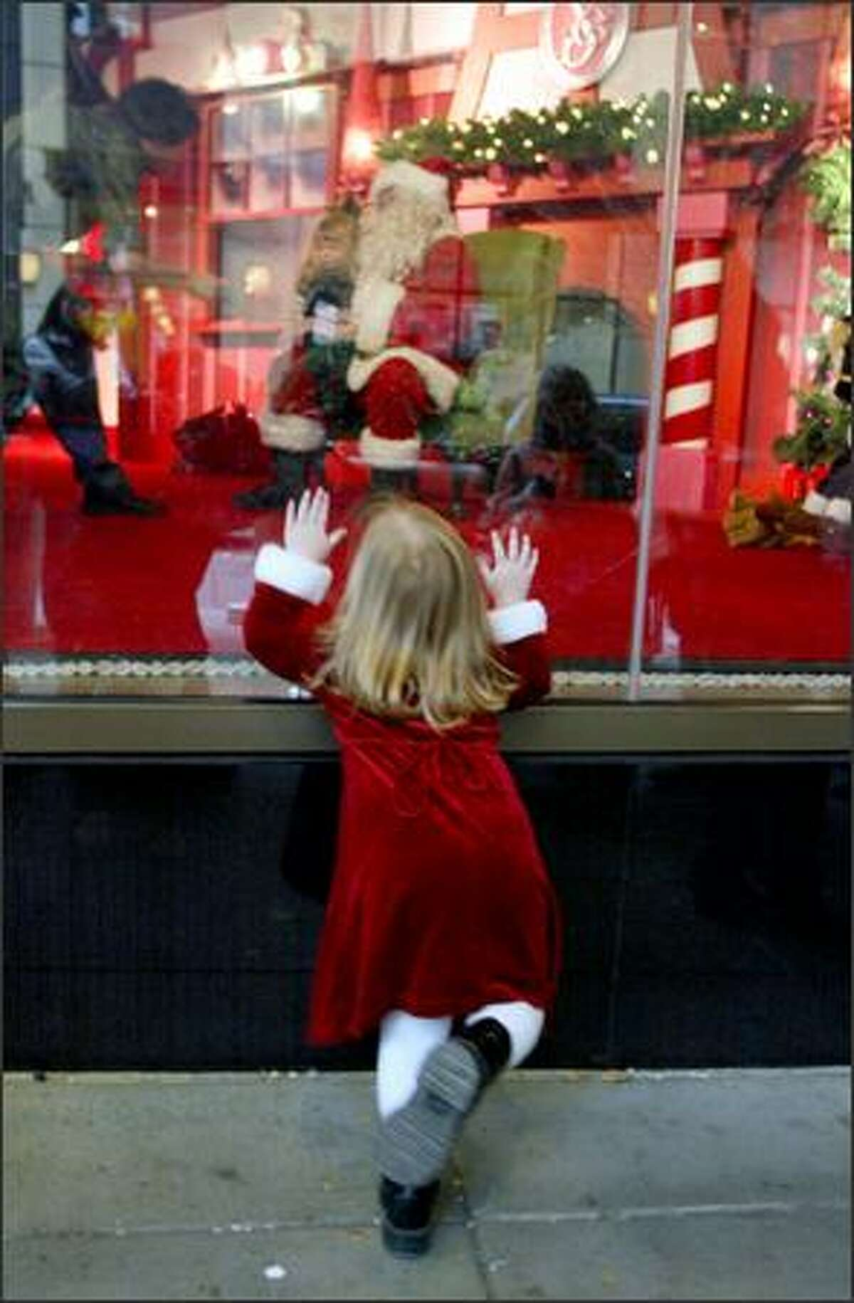 Antsy with anticipation, Lydia Nelson, 2, of Maple Valley looks in at Santa Claus as she waits in line to have her and her sister's photograph taken with him at Nordstrom in downtown Seattle.