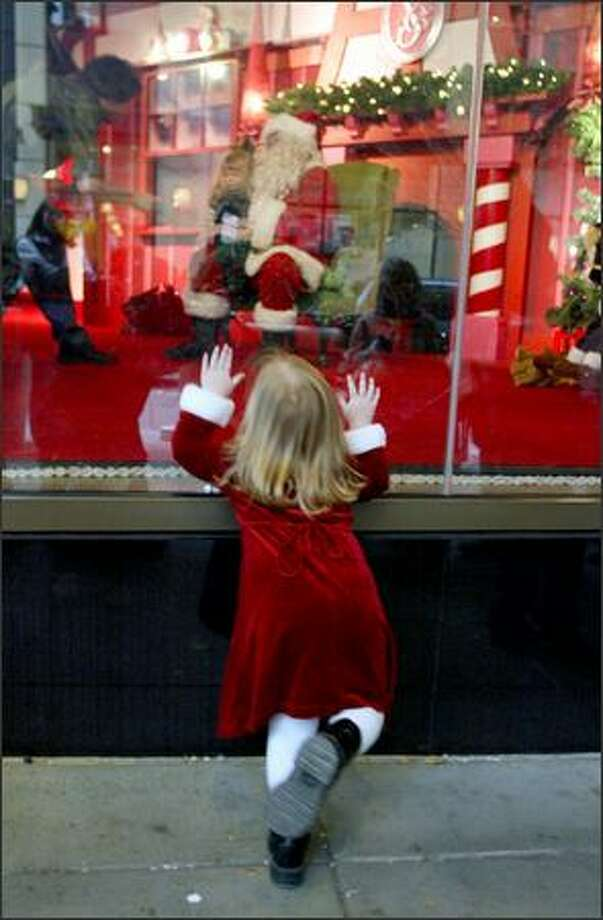 Antsy with anticipation, Lydia Nelson, 2, of Maple Valley looks in at Santa Claus as she waits in line to have her and her sister's photograph taken with him at Nordstrom in downtown Seattle. Photo: Meryl Schenker, Seattle Post-Intelligencer / Seattle Post-Intelligencer