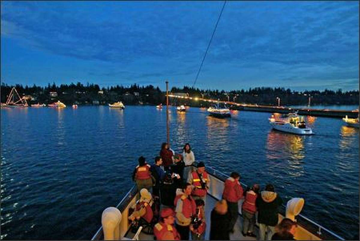Passengers gather on the bow of the Virginia 4 to watch the decorated boats of the 34th annual Special People's Holiday Cruise cross the waters of Lake Washingon toward the SR 520 bridge, going around a large sailboat, left, anchored off Medina. More than 2,000 developmentally disabled adults boarded 200 boats for the event.