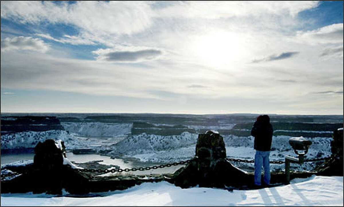 A bird-watcher scans the waters below the freshly snow-powdered basalt of Dry Falls from the Dry Falls Overlook in Grant County, one of 53 recommended birding sites on the Coulee Corridor map of the Audubon Society's Great Washington State Birding Trail.