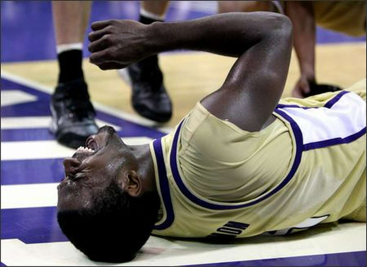 Justin Dentmon goes down with a leg cramp late in the game as the University of Washington beat Southern Utah University 87-72 at Bank of America Arena on Monday.