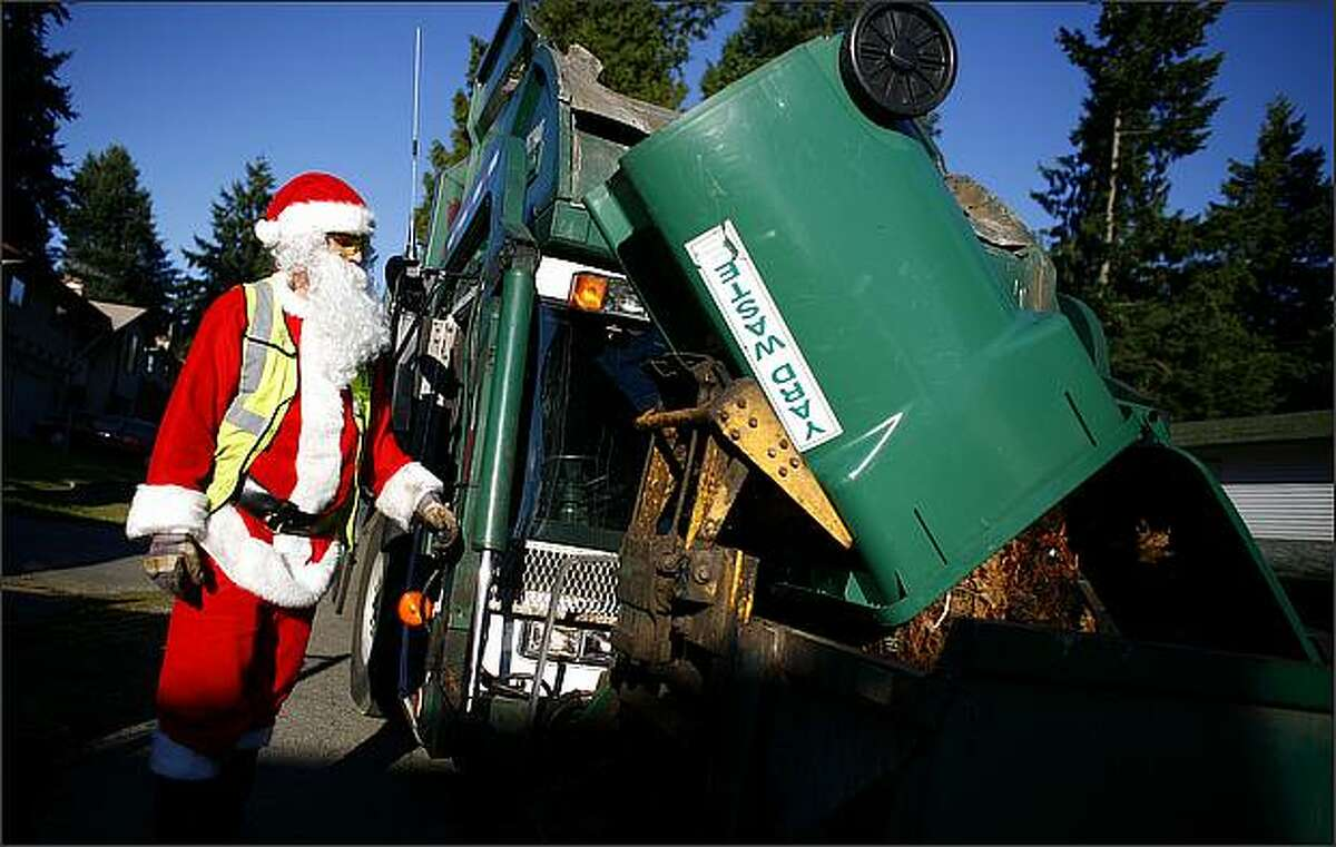 Santa, aka, Nic Greer, an employee of Waste Management, empties yard waste bins during trash day. This is Greer's second year of dressing as Jolly Old Saint Nick during December garbage pickups.