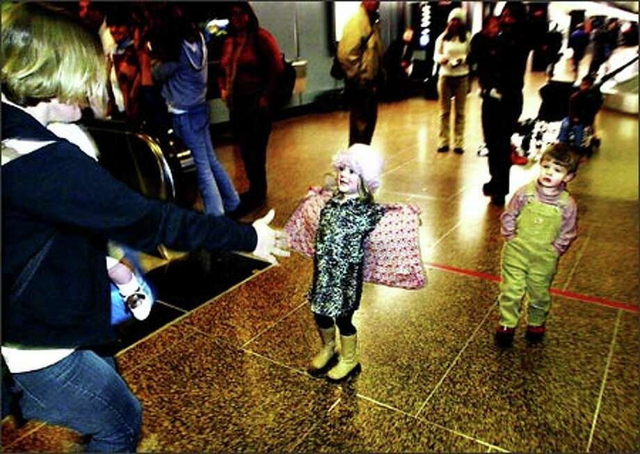 "Kylee English (center), 4, greets her mother Army Specialist Leah English (left) as her brother, Blake, 2, looks on, by showing her her new ""army"" dress as  English arrives at Sea Tac Airport.  English has been on assignment in  Iraq but is on a quick two-week leave after her grandfather died. Photo: Karen Ducey, Seattle Post-Intelligencer / Seattle Post-Intelligencer"