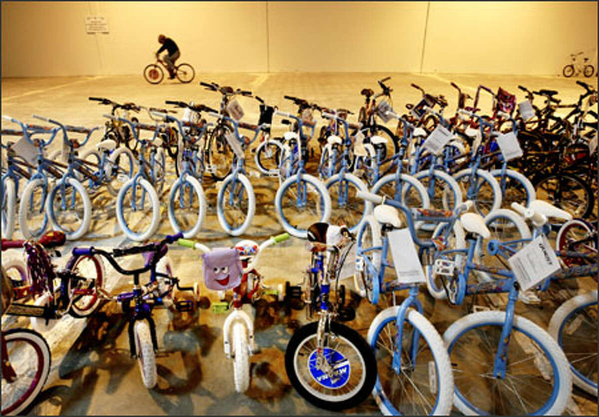In a Canyon Park warehouse, Cindie Murphy test-rides a bike that will soon become a gift for a needy youngster through the Forgotten Children's Fund.