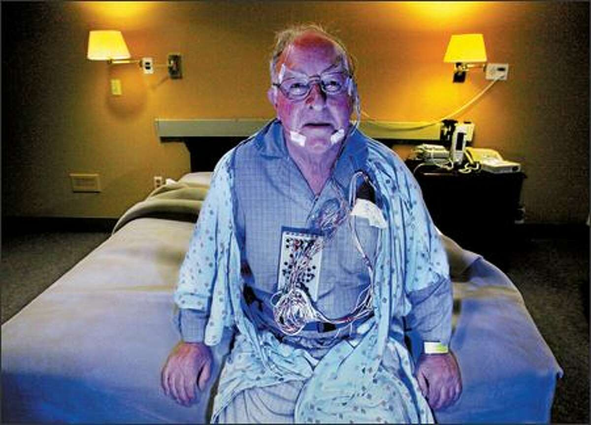 Michael Tyler, 79, wears the bulky equipment necessary for a sleep study at Virginia Mason Medical Center in Seattle. His heart, brain waves, eye and leg movements were monitored on his first night at the hospital in an effort to get to the bottom of his sleep disorder. He spent a second night there trying out treatments.
