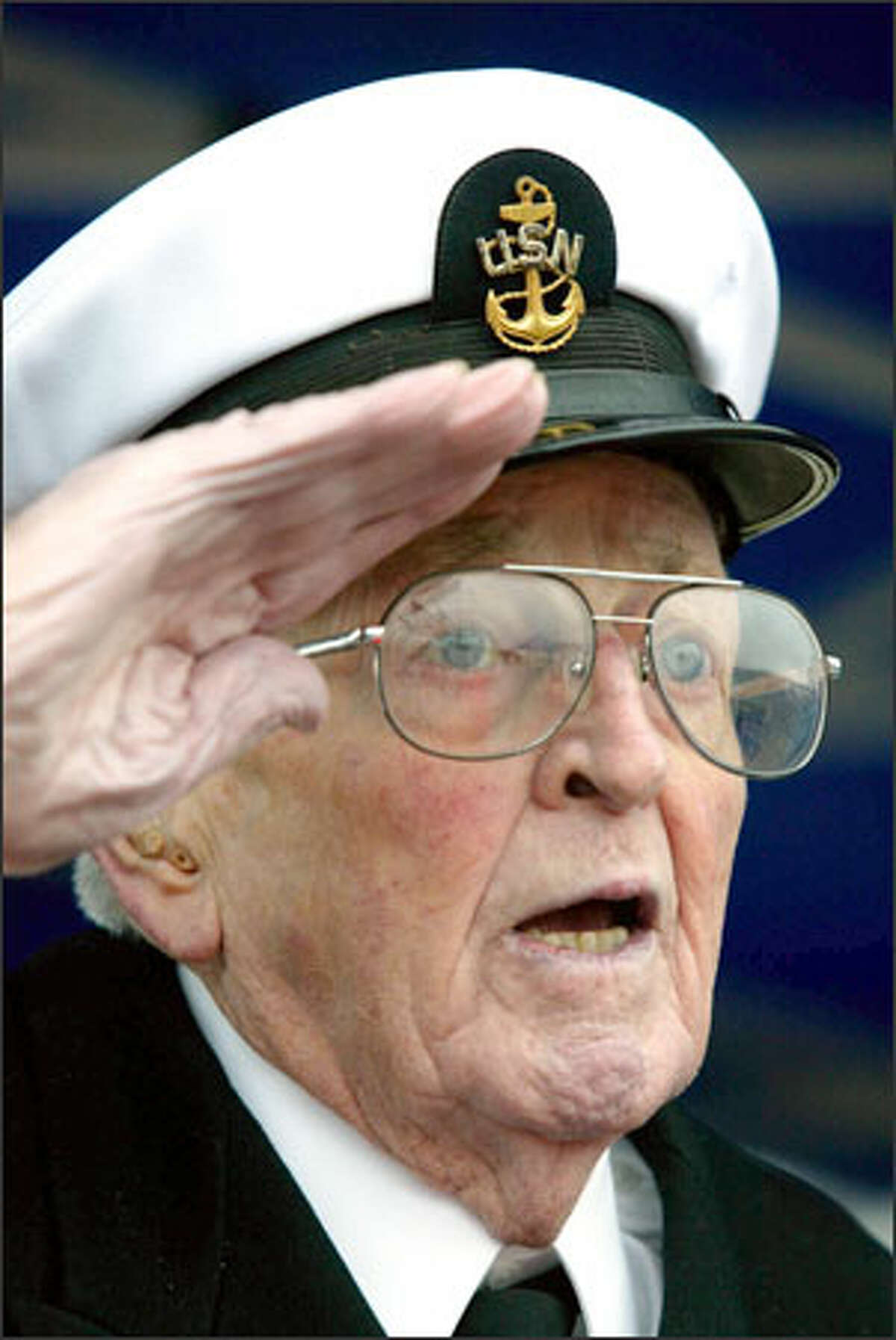 Retired Chief Petty Officer William Brown, 85, salutes and recites the Pledge of Allegiance during Pearl Harbor Memorial Day activities at Naval Station Everett. He and a handful of other Pearl Harbor survivors were honored.