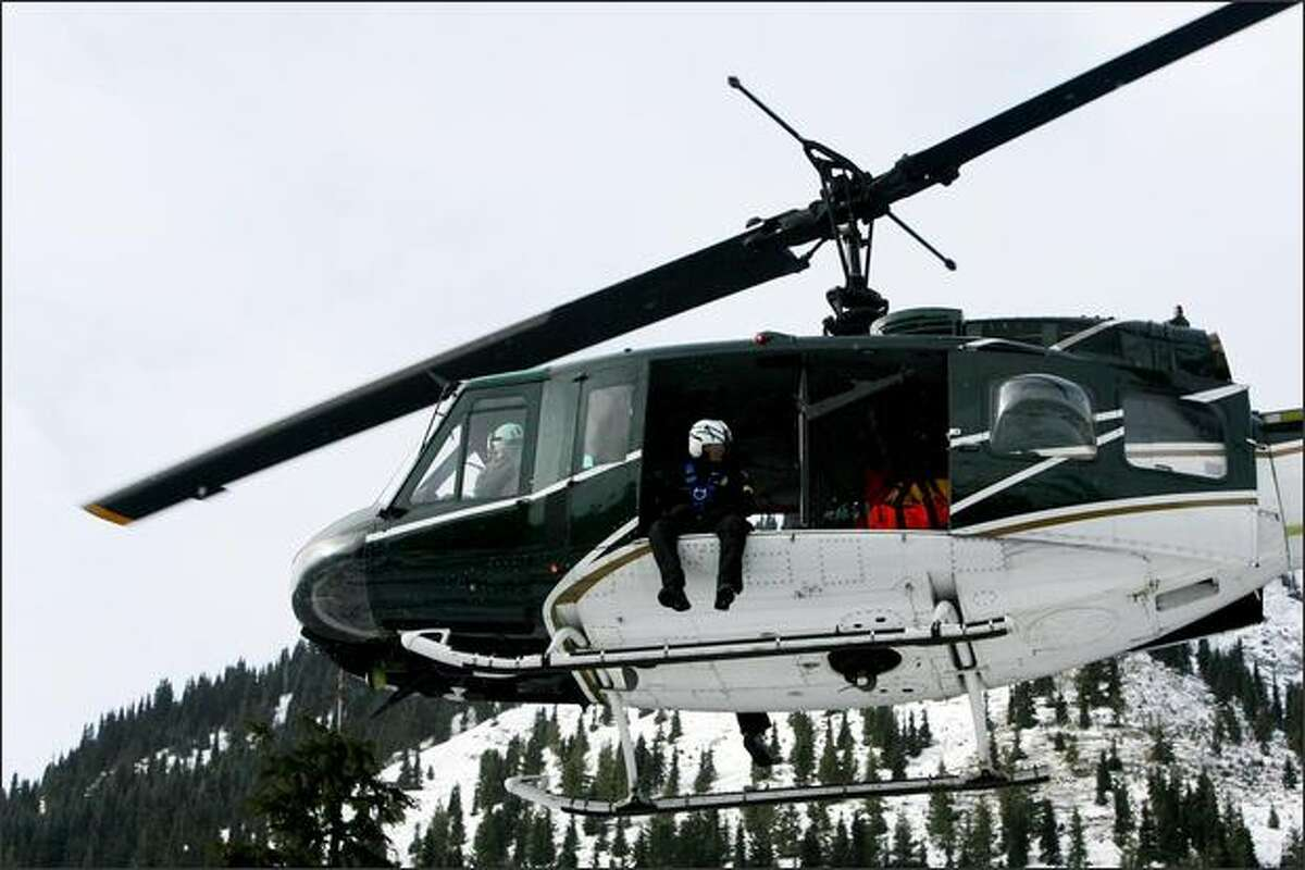 A helicopter from the King County Sheriff's office help in the search for three missing snowboarders on Crystal Mountain.