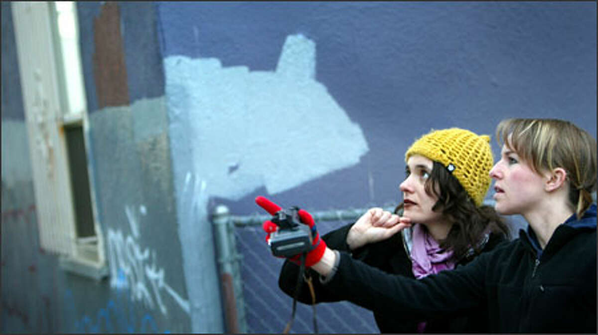 University of Washington doctoral candidate Giorgia Aiello, left, and undergraduate student Emily Fischer contemplate graffiti in an alley behind University Way Northeast businesses as a buffed, or repainted, wall rises behind them. The graffiti are documented before being painted over.