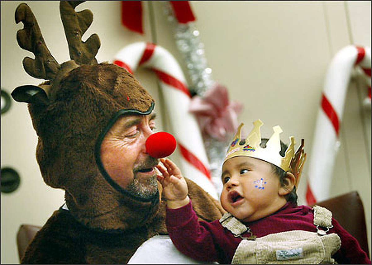 Rudolph the Red Nosed Reindeer (aka Larry Watson, an administrator in Harborview Medical Center's Department of Psychiatry) gets some close scrutiny from 7-month-old German Castro during the hospital's annual Children's Holiday Party. About 800 of the hospital's youngest patients, infants to age 10, enjoyed activities and received gifts at the event Tuesday.
