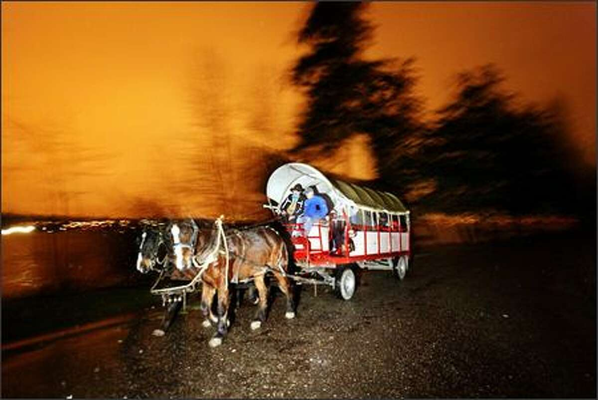 Gerhard Jorgenson, left, guides the wagon around Seward Park for the Holiday Hayrides.