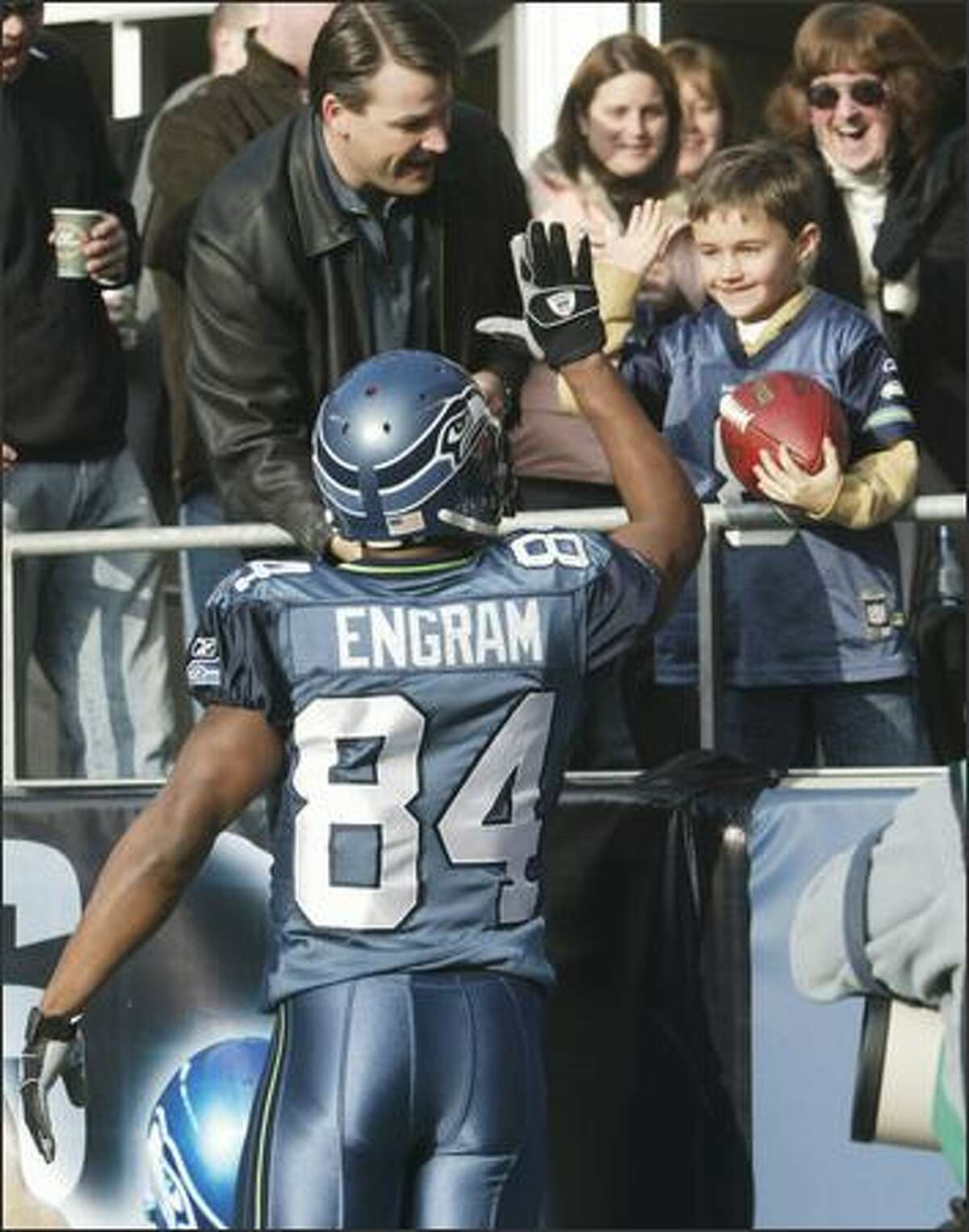After scoring a touchdown and handing him the football, Seahawks' Bobby Engram gives Gabe Lysen, 7, a high five. With Gabe is his dad Zac Lysen.