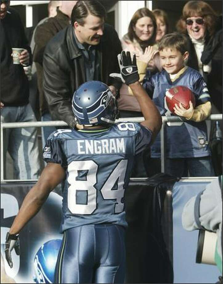 After scoring a touchdown and handing him the football, Seahawks' Bobby Engram gives Gabe Lysen, 7, a high five. With Gabe is his dad Zac Lysen. Photo: Dan DeLong, Seattle Post-Intelligencer / Seattle Post-Intelligencer