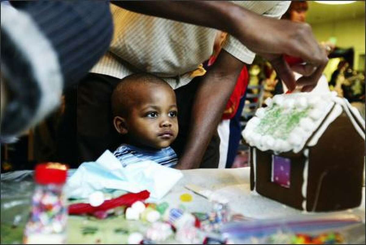 Christopher Watkins watches his father Cassius Watkins build a gingerbread house as part of a holiday celebration sponsored by