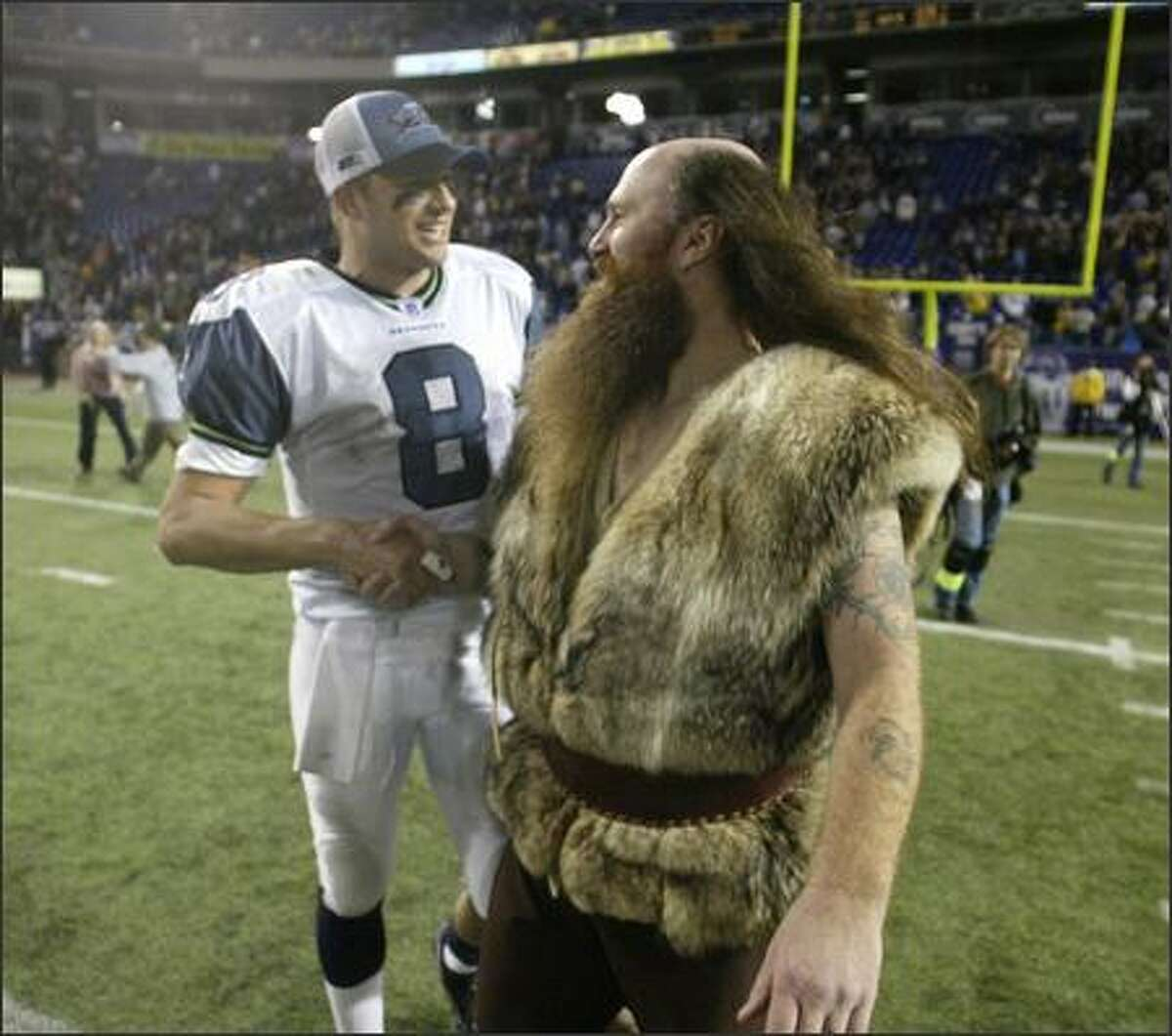 Seahawks quarterback Matt Hasselbeck shakes hands with the Minnesota Vikings' mascot, Ragnar. Hasselbeck completed 23 of 34 passes in leading the Seahawks to their 27-23 victory.