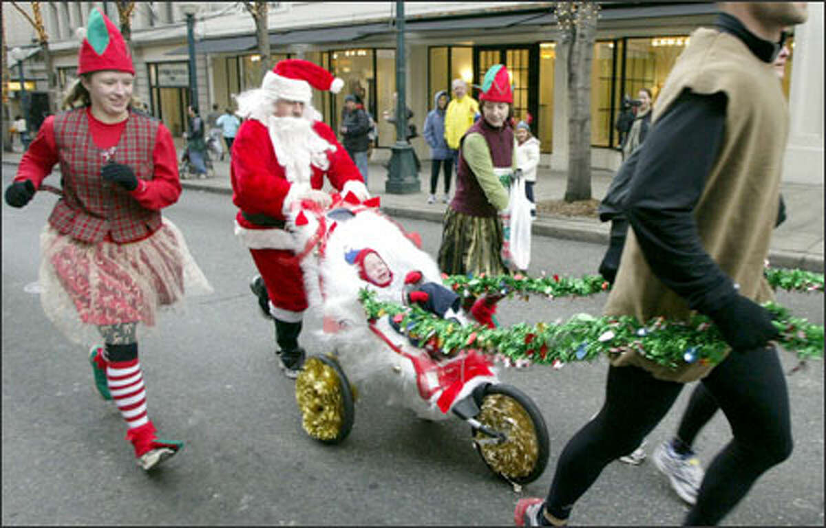 With joggers in front dressed as reindeer, and elves to each side, Santa Claus pushes a jogging stroller resembling a sleigh down Fifth Avenue during the 20th annual Jingle Bell Run. More than 10,000 runners and walkers showed up in downtown Seattle to raise money to support research, programs and services for the Arthritis Foundation.