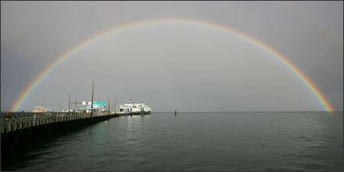 A massive rainbow encompasses the Vashon Island ferry dock and the ferry Issaquah after a hard rain shower.