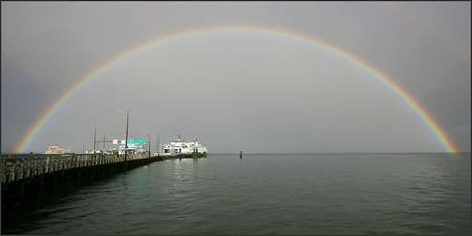A massive rainbow encompasses the Vashon Island ferry dock and the ferry Issaquah after a hard rain shower. Photo: Mike Urban, Seattle Post-Intelligencer / Seattle Post-Intelligencer