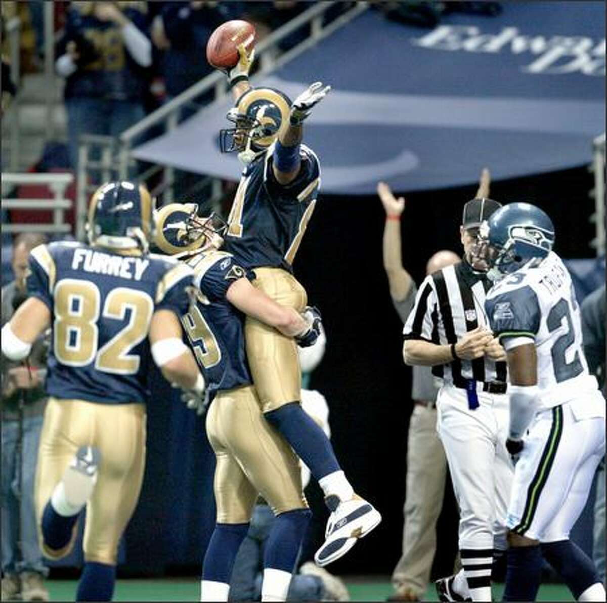 Torry Holt -- the NFL's leading receiver --celebrates with teammate Dane Looker of Puyallup after giving the Rams a 21-9 lead.