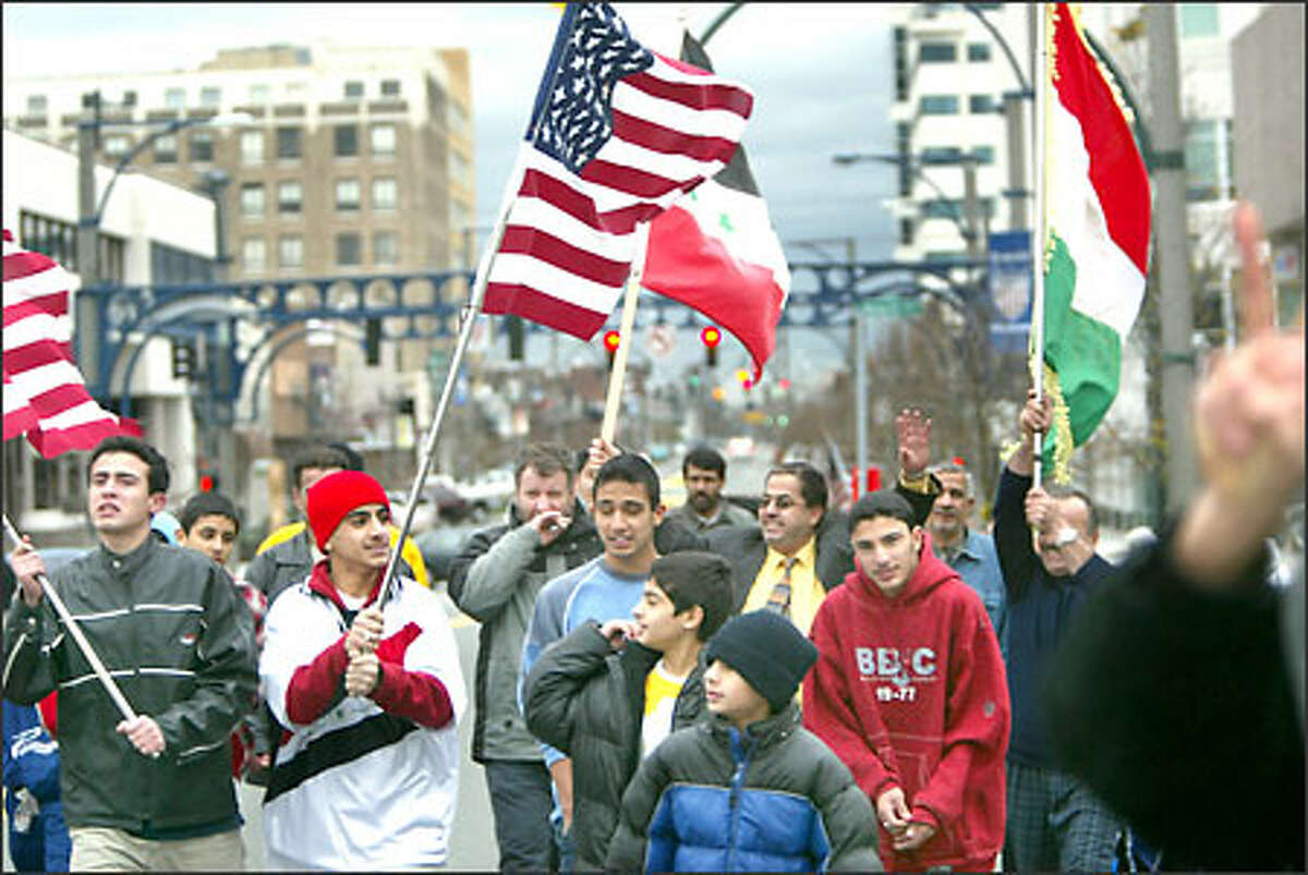 Members of the Iraqi American community celebrate in downtown Everett. The celebration began early yesterday morning.