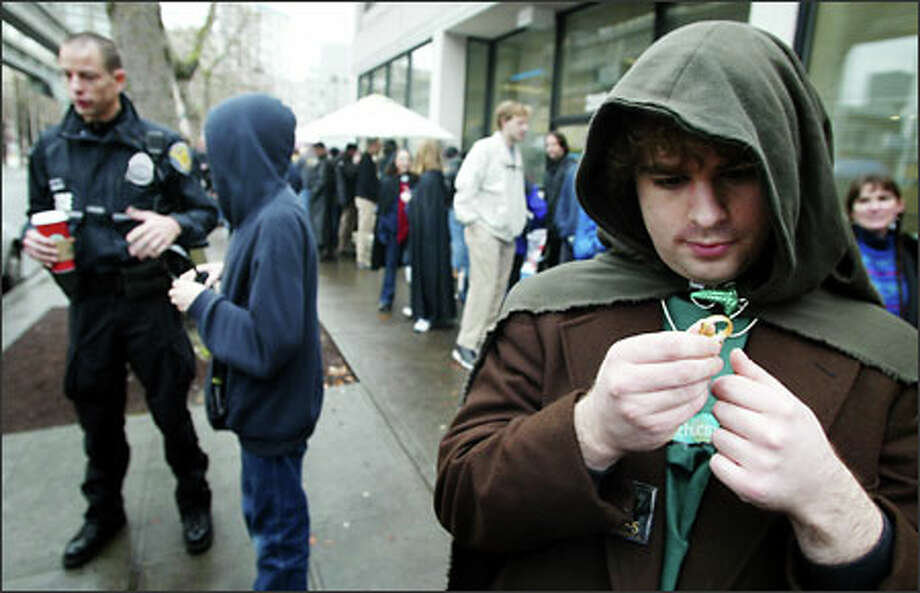 "Self-described ""Lord of the Rings"" fanatic Casey Jepson, dressed as hobbit Frodo Baggins, admires his precious ""One Ring"" while waiting in line to enter the Cinerama in downtown Seattle. The theater plans to show the first two movies in the Lord of the Rings trilogy and then cap the evening with a 10 p.m. premiere of the new movie, ""The Return of the King."" One fan said he was in line since Saturday morning. Photo: Joshua Trujillo, Seattlepi.com / seattlepi.com"