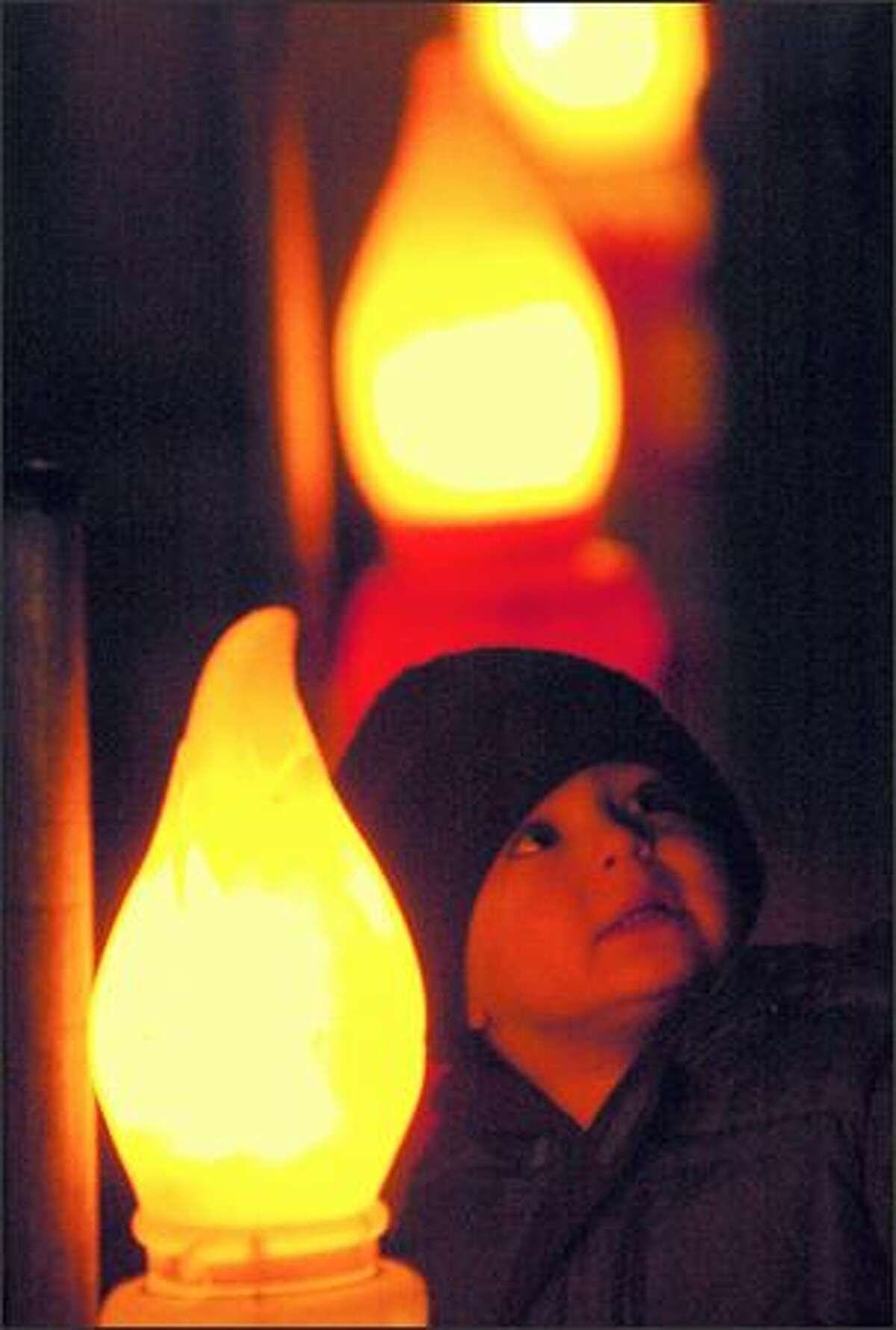 Two-year-old Ethan Cherry is bathed in light from a row of electric candles at