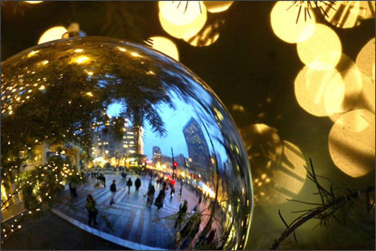 As the last weekend before the holiday begins, an ornament on a Christmas tree reflects people at Seattle's Westlake Center. Stores will be hoping for a last-minute rush in the coming week.