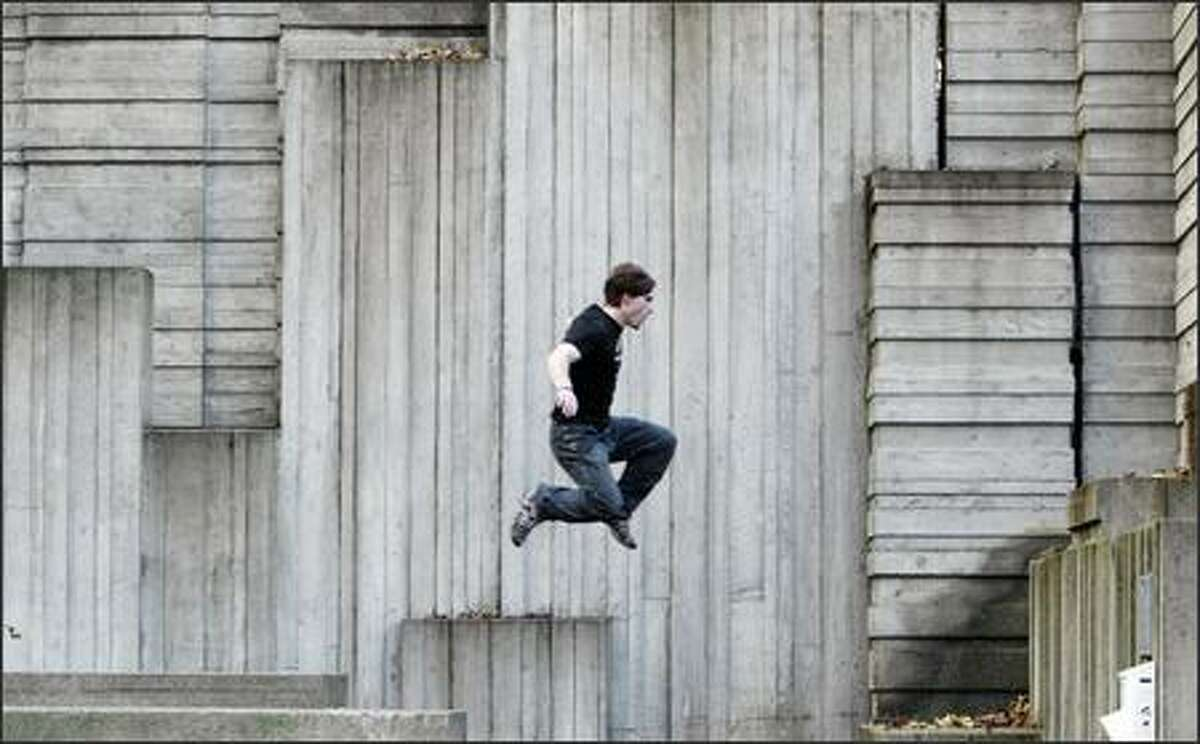 """University of Washington student Tyson Cecka, 19, leaps from one concrete pile to another while doing parkour in Seattle's Freeway Park on Sunday. """"You have to overcome fear. The world is our obstacle course. You see things other people do not,"""" Cecka says."""