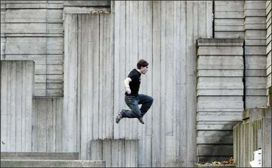 "University of Washington student Tyson Cecka, 19, leaps from one concrete pile to another while doing parkour in Seattle's Freeway Park on Sunday. ""You have to overcome fear. The world is our obstacle course. You see things other people do not,"" Cecka says. Photo: Gilbert W. Arias, Seattle Post-Intelligencer / Seattle Post-Intelligencer"