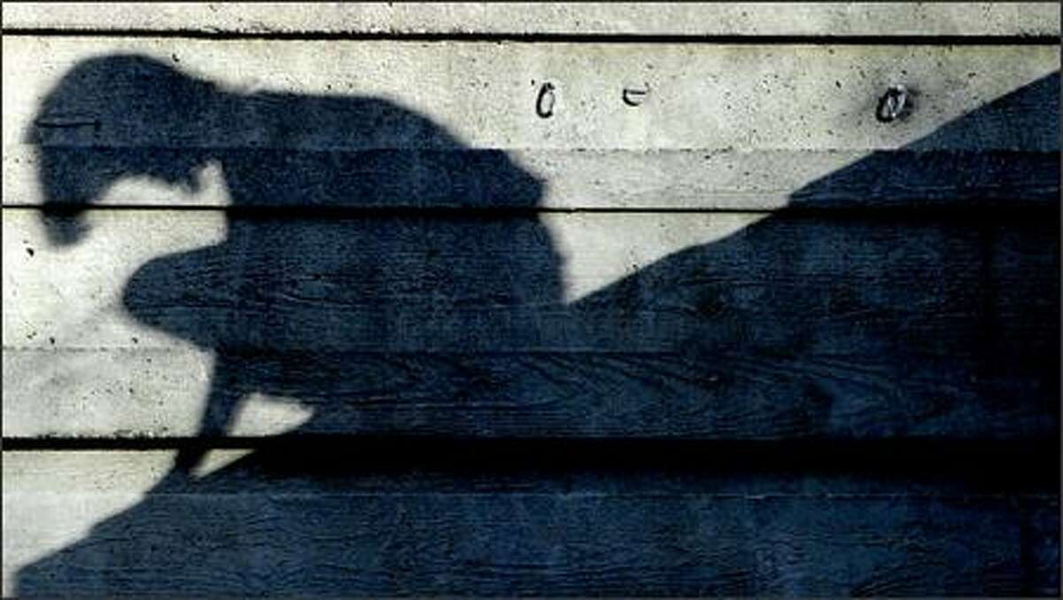 The shadow of Janine Cundy is cast on a concrete wall as she gets set to make a leap while taking part in parkour in Seattle Sunday.