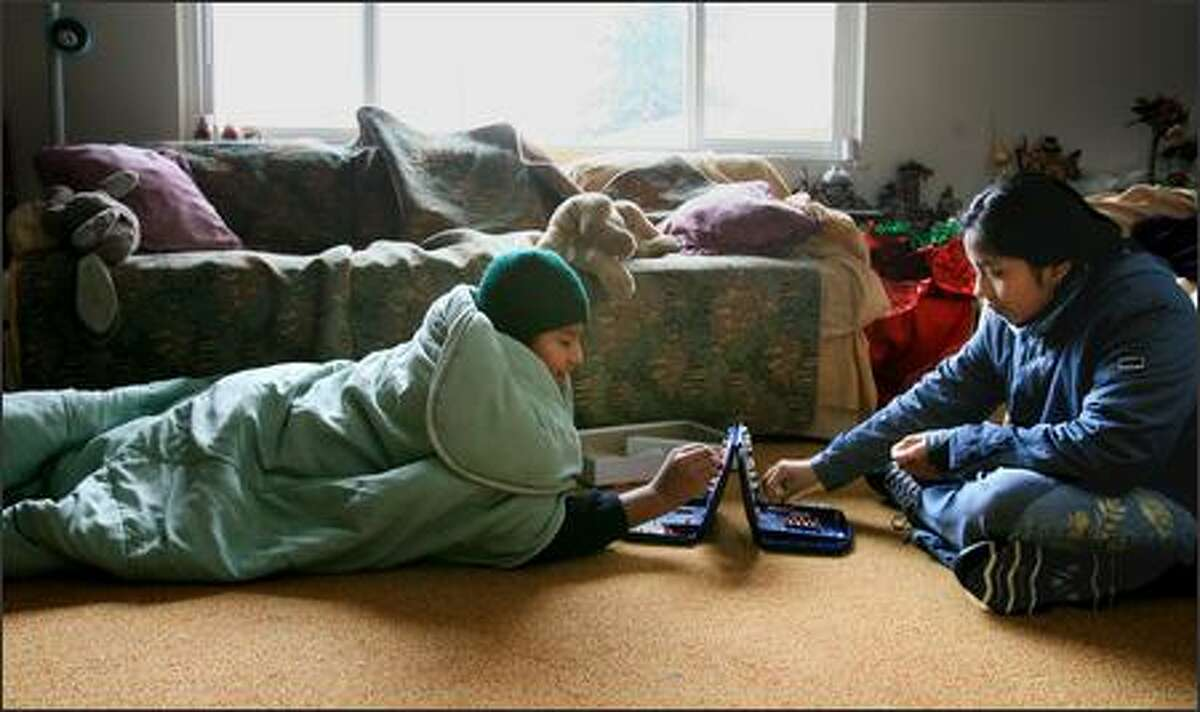 Roberto Perez, 12, and his sister Mirsa, 10, try to stay warm as they play a game of Battleship to pass time. The family has had no electricity at their apartment since Thursday.