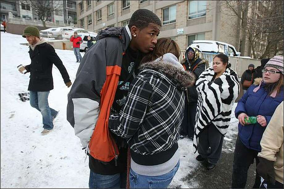Seattle Police and Fire Department respond to an accident in which a couple of charter buses with dozens of people aboard slid down the snow-covered cobblestones of Thomas Street on Capitol Hill and crashed into each other, crashing through a guard-rail on Melrose Street 20 to 30 feet above I-5.(l-r) Devonte Pearson of Tacoma hugs his friend, Shaylynn Patom of Centralia as they wait for their luggage. They were both passengers on one of the buses. Photo: Mike Kane, Seattle Post-Intelligencer / Seattle Post-Intelligencer