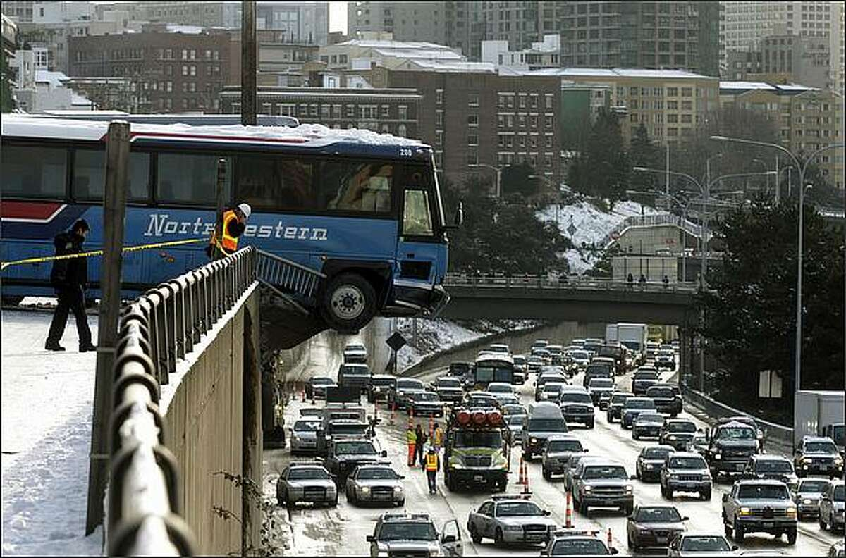Two buses slide down an icy East Thomas Street, one crashing through the guard rail and suspended over Interstate 5 in Seattle.